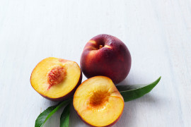 Two fresh peaches with one sliced in half, revealing the pit