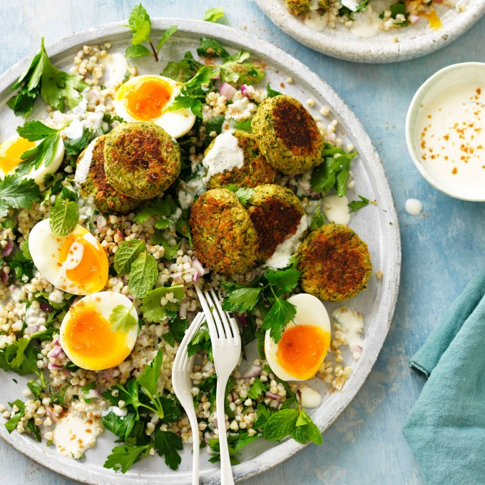 Baked falafel on plate with salad, fresh herbs and eggs